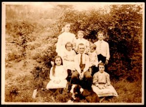 Livingston Family, at Escanaba Michigan seated in or beside large chair: Helen, Jenny, Archie, Edward James, Ruth standing behind: Mary, Louis, George